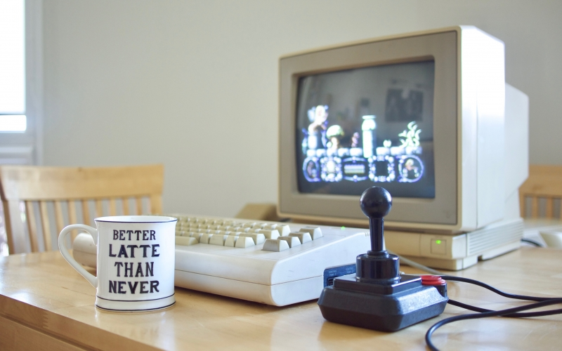 old computer, retro computer, desk, room, cup, commodore 64g, commodore 1802 display, competition pro joystick, stormlord, video game, screen