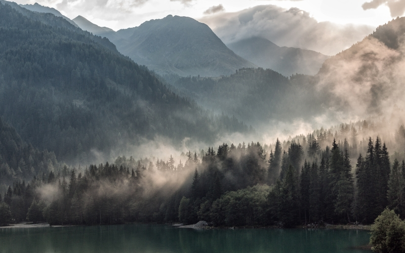 wood, lakeside, antholz, sun rays, fog, water, trees, mountains, hills, mist, sunshine, forest, nature